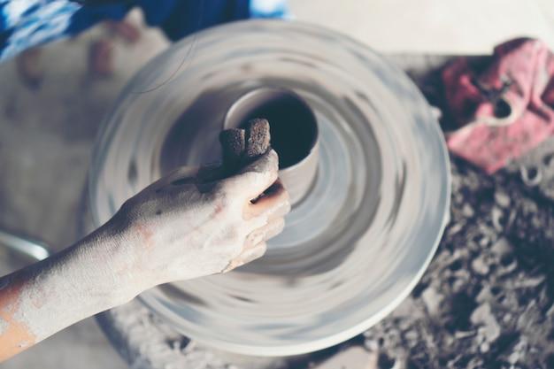 Les mains de la femme se ferment, l'atelier de maîtrise de la céramique travaille avec de l'argile Photo Premium