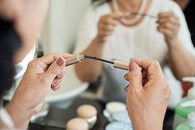 Mains d'une femme senior méconnaissable tenant un mascara devant un miroir Photo gratuit