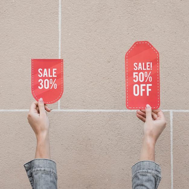 Mains de femme avec des signes de vente Photo gratuit