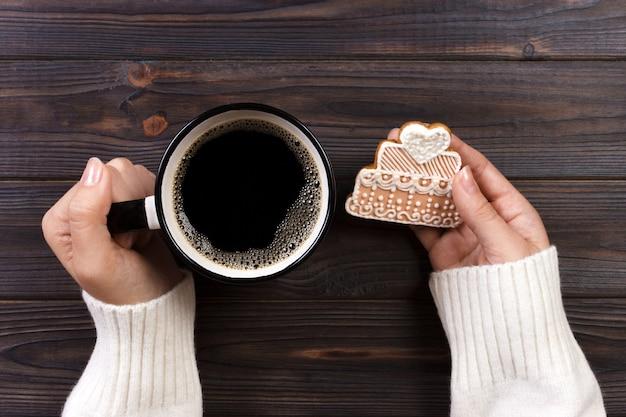 Mains de femme avec une tasse de café avec des biscuits Photo Premium