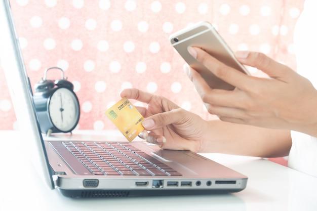 Mains De Femme Sur Téléphone Portable Et Carte De Crédit En Plastique. E-paiement. Shopping En Ligne Photo Premium