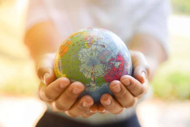 Mains de femme tenant la boule du monde sur sa main avec un fond vert naturel. concept de la journée mondiale de l'environnement. Photo Premium