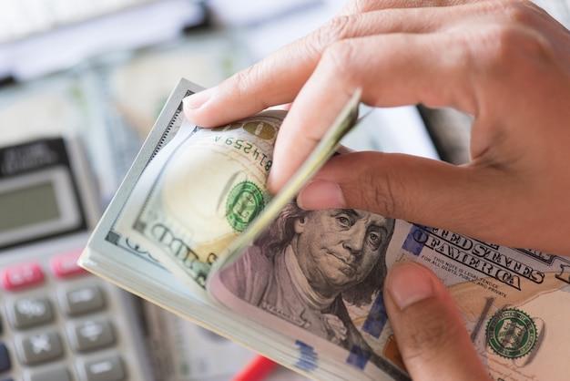 Mains de femme tenant et comptant des tas de billets de dollars américains. Photo Premium