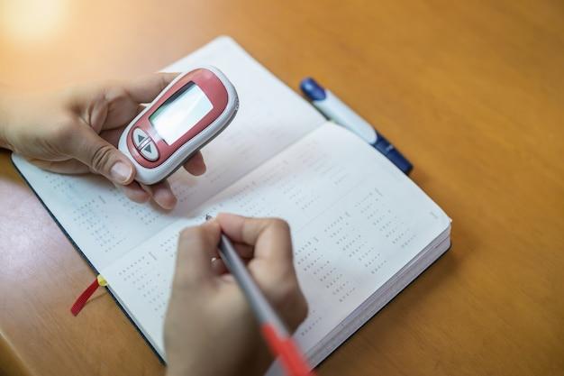Mains de femme tenant un glucomètre et un stylo pour écrire un programme de contrôle du taux de glycémie Photo Premium