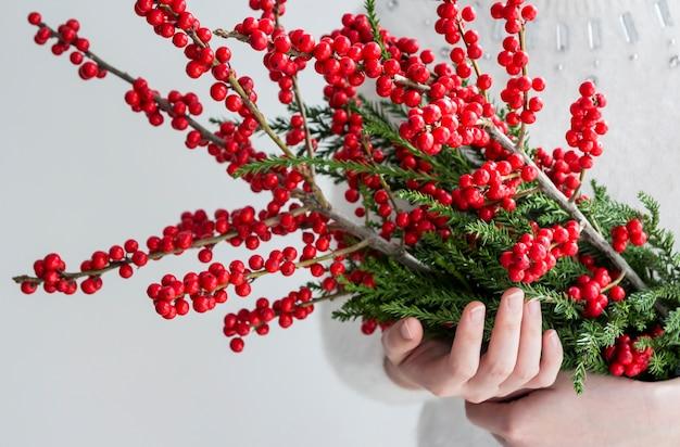 Mains de femme tenant ilex verticillata ou winterberry pour la décoration de noël Photo Premium
