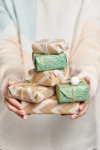 Les mains de la femme tiennent des boîtes-cadeaux. boîte cadeau décorée pour noël ou le nouvel an. Photo Premium