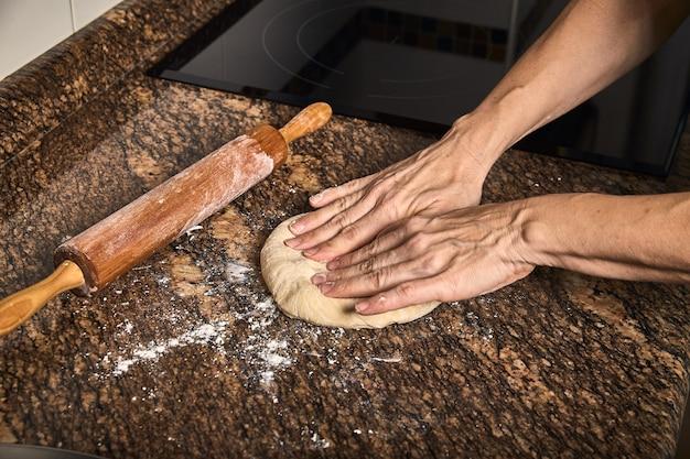 Mains de femme travaillant sur une pâte pour cuire une pizza savoureuse Photo Premium