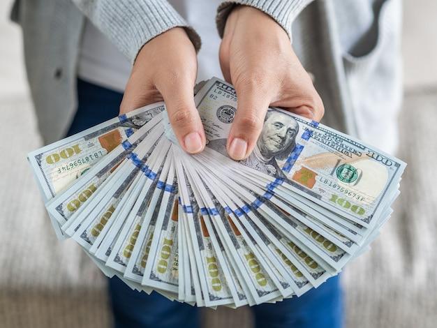 Des mains de femme vous proposent de l'argent en dollars. Photo Premium