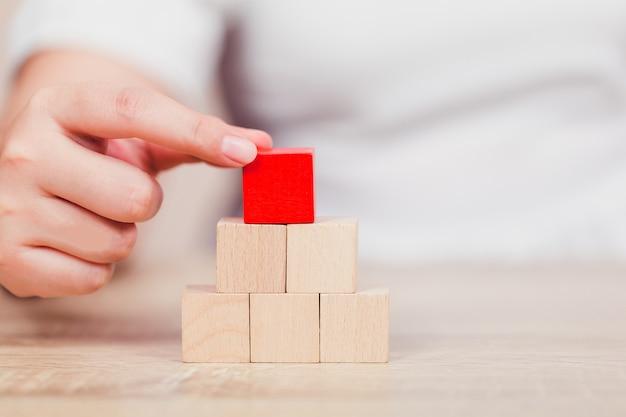 Mains de femmes, empilant des blocs de bois en marches. Photo Premium