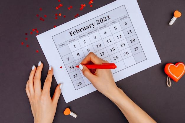 Les Mains Des Femmes Entouraient Le Numéro 14 Du Calendrier Avec Du Rouge à Lèvres. La Saint-valentin. Photo Premium