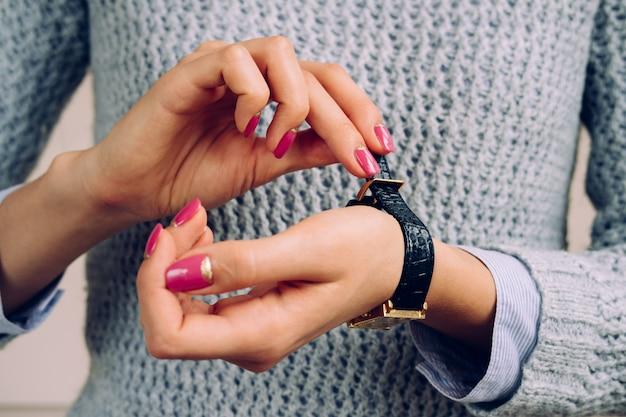Les mains des femmes avec une manucure brillante attache le bracelet à la montre Photo Premium