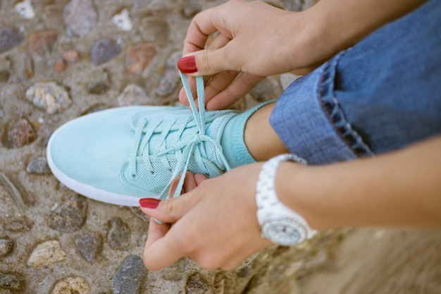Mains de femmes avec une manucure rouge lacets noués sur des chaussures de sport Photo Premium