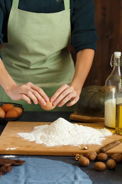 Les mains des femmes pétrissent la pâte. le pâtissier enfonce un œuf dans la farine. sur la table en bois sont des ingrédients de cuisson. Photo Premium