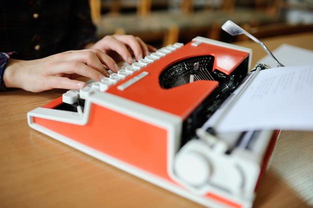 Les mains des femmes sont imprimées sur une machine à écrire en gros plan rouge. livres d'écriture Photo Premium