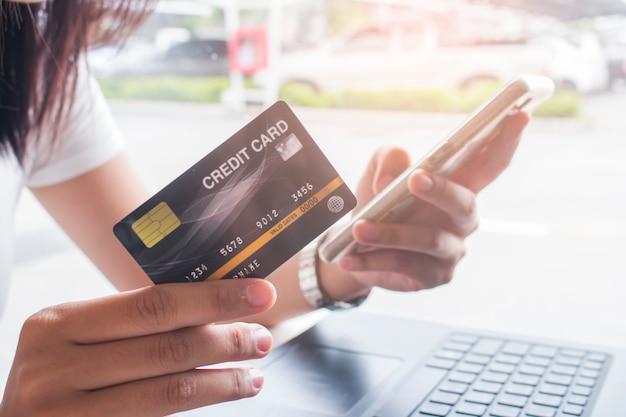 Mains de femmes tenant un smartphone et utilisant une carte de crédit Photo Premium