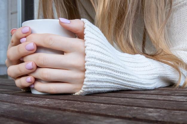 Mains De Femmes Tenant Une Tasse De Café Ou Une Tasse De Thé Sur Une Table En Bois. Photo Premium