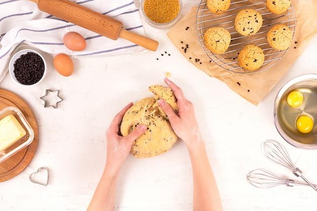 Les mains des femmes tiennent la pâte pour faire des biscuits. equipement et ingrédients culinaires. œufs, farine, sucre, chocolat, beurre, plats de cuisson. lay plat. Photo Premium