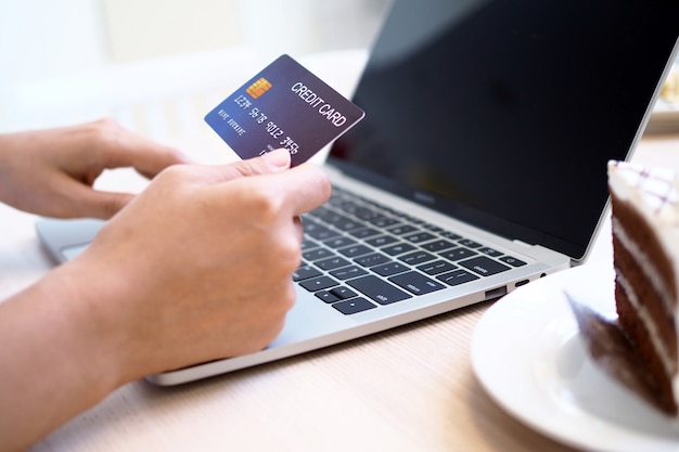Les mains des femmes utilisent des ordinateurs et des cartes de crédit pour commander des produits en ligne. Photo Premium