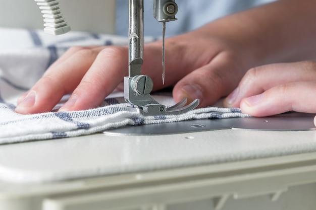 Mains d'une fille coud sur un gros plan de machine à coudre blanc sur un fond bleu avec mise au point sélective de l'espace de copie Photo Premium
