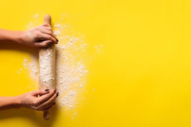 Les mains de la fille gardent le rouleau à pâtisserie avec de la farine sur fond jaune. Photo Premium