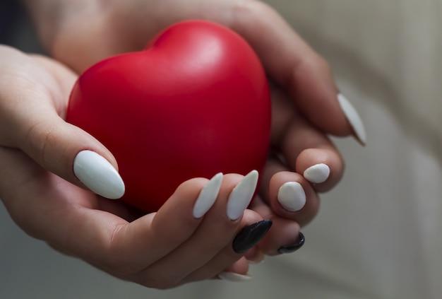 Mains de la fille tenant coeur rouge Photo Premium