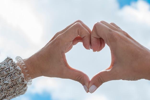 Mains formant un coeur vers le ciel Photo Premium