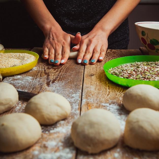 Mains Formant La Pâte Afin De Préparer La Vue Latérale Du Bagel Turc Simit. Photo gratuit
