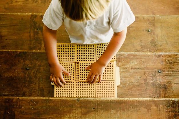 Mains de garçon manipulant compter les cubes sur fond en bois en classe de montessori Photo Premium