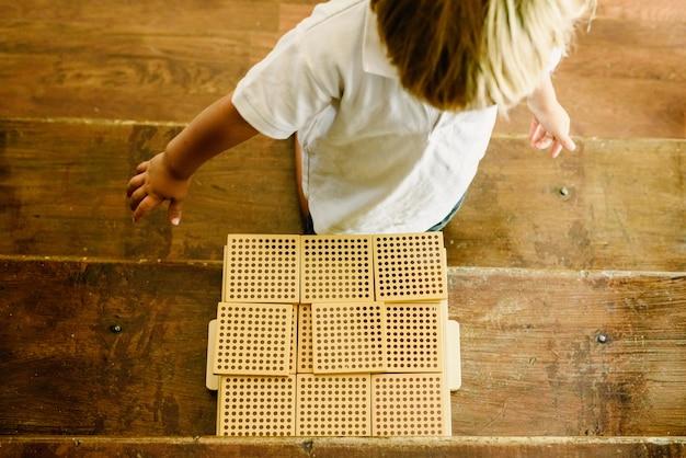 Mains de garçon manipulant des cubes de comptage sur fond en bois en classe montessori Photo Premium