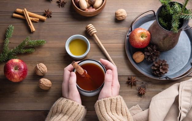 Mains Gardent Une Tasse D'arôme De Thé Aux Pommes De Noël à La Cannelle Sur Une Table En Bois. Vue De Dessus Photo Premium