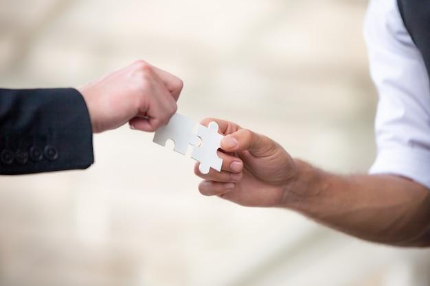 Les mains des gens d'affaires détiennent ensemble puzzle en papier, l'équipe des affaires se réunissant jigsaw Photo Premium