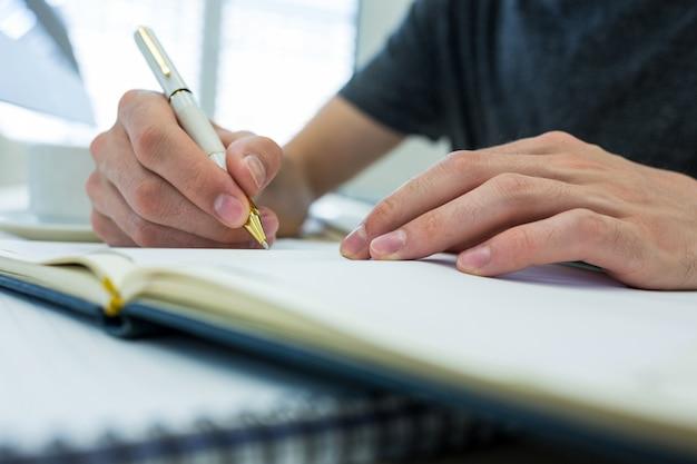 Mains de graphiste mâle écrivant sur un journal Photo gratuit