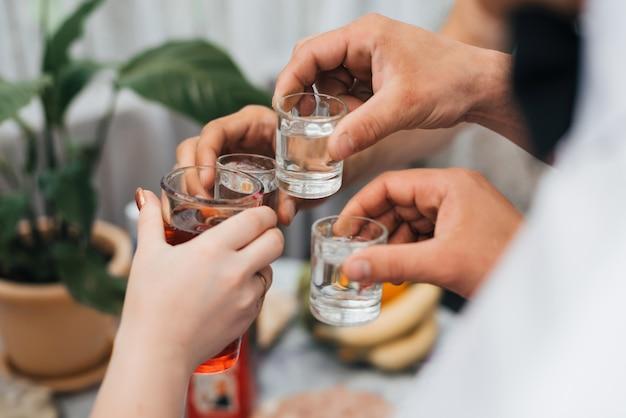 Mains, groupe, amis, cliquetis, lunettes, de, vodka Photo Premium