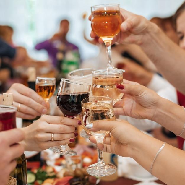 Mains d'un groupe d'amis tinter des verres de vin et de grillage Photo Premium
