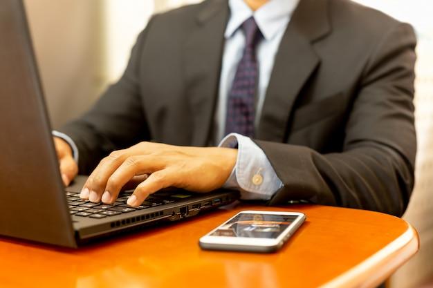Mains d'homme d'affaires tapant sur un ordinateur portable clavier avec un téléphone portable sur le bureau en bois. Photo Premium