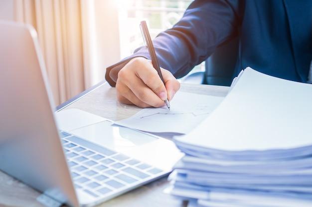 Mains d'homme d'affaires travaillant et écrivant des données dans l'ordinateur, piles de fichiers papier pour la recherche Photo Premium