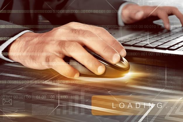 Mains d'homme d'affaires travaillant avec une souris sans fil et un ordinateur portable Photo Premium