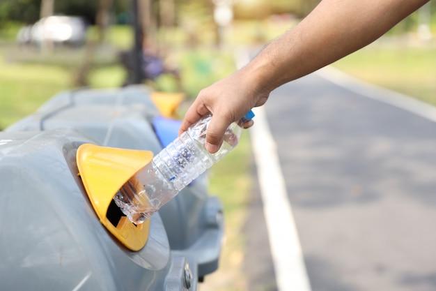 Des mains d'homme jettent une bouteille en plastique vide à la poubelle Photo Premium