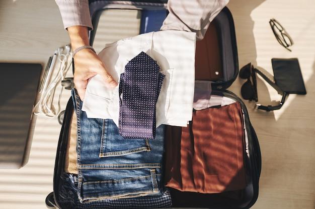 Mains d'homme méconnaissable emballant la valise pour le voyage Photo gratuit