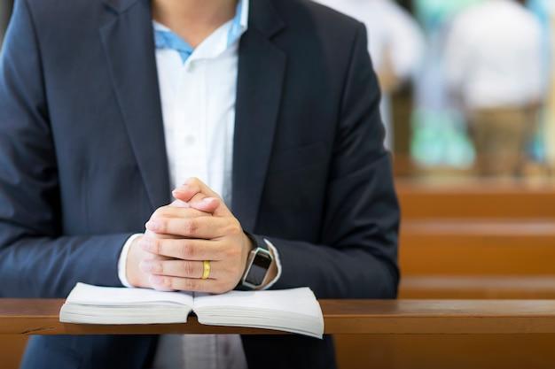 Des mains d'homme priant sur une sainte bible dans l'église pour le concept de la foi, la spiritualité et la religion chrétienne. Photo Premium