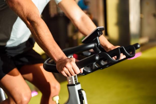 Mains d'un homme s'entraînant dans un gymnase faisant du cyclo indoor. Photo gratuit