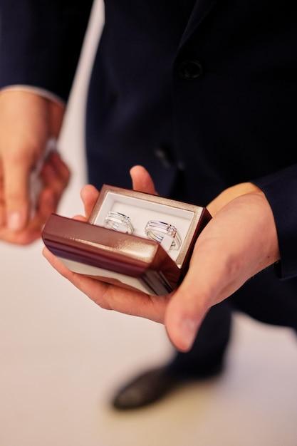 Mains d'homme tenant une boîte blanche avec des alliances Photo Premium