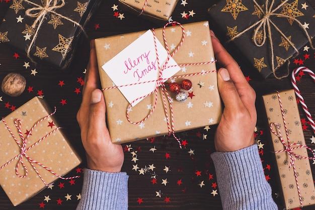 Mains D'homme Tenant Une Boîte De Cadeau De Vacances De Noël Avec Carte Postale Joyeux Noël Sur La Table De Fête Décorée Photo gratuit