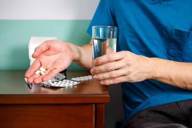 Mains Homme En Tenant La Pilule Et Le Verre D'eau Sur La Table Alors Qu'il était Assis Sur Le Canapé Et Va Prendre Des Médicaments Photo Premium