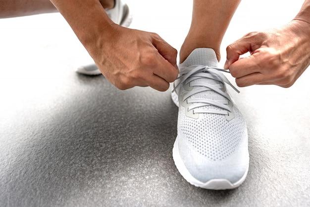 Les mains des hommes attachant le lacet sur les chaussures de course avant la pratique. le coureur se prépare pour l'entraînement. mode de vie actif de l'athlète sportif. Photo Premium