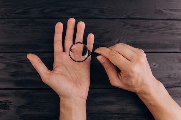 Les mains des hommes sur un bureau noir rustique tenant une loupe. Photo Premium