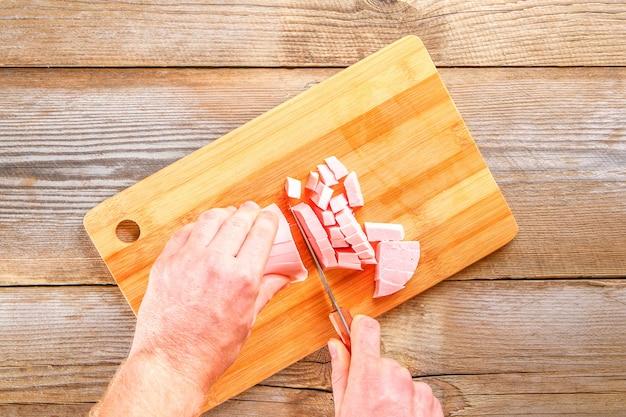 Les mains des hommes coupent la saucisse bolognaise sur une planche à découper Photo Premium