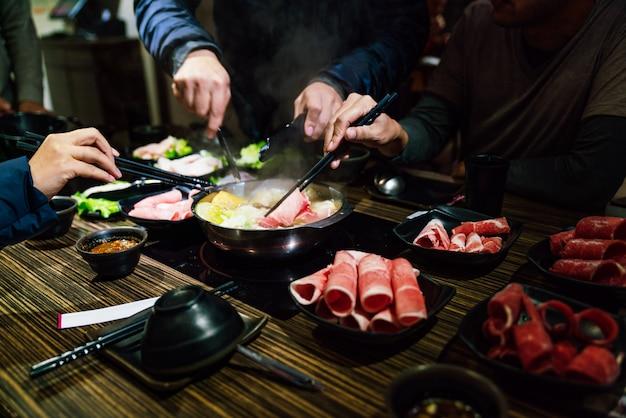 Mains d'hommes et de femmes pinçant une tranche de bœuf wagyu a5 et de porc kurobuta de taille moyenne dans un hot pot shabu. Photo Premium
