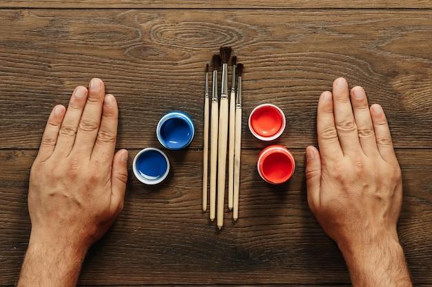 Mains d'hommes, pinceaux et peinture ouverte sur une table en bois marron Photo Premium