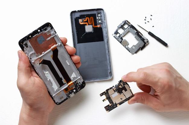 Les Mains Des Hommes Tiennent Un Tournevis Dans Leurs Mains Et Réparent Le Smartphone Cassé Photo Premium